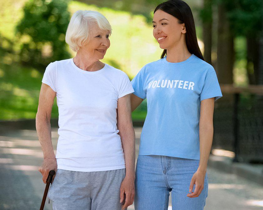 Smiling woman volunteer t-shirt and happy aged lady walking nursing home garden